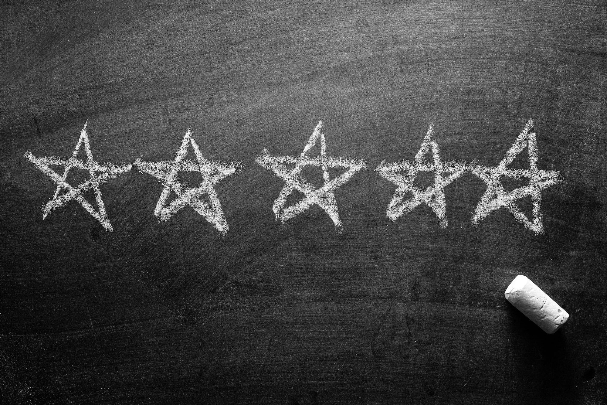 Line of five stars hand drawn on a blackboard
